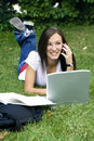 Cute teen girl laying down on the grass studying Royalty Free Stock Images