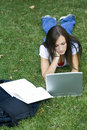 Cute teen girl laying down on the grass studying Stock Image