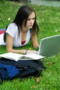 Cute teen girl laying down on the grass studying Royalty Free Stock Photos