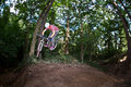 Cute teen jumping with his bike over a natural ramp in the fores forest Royalty Free Stock Photography