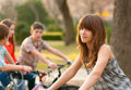 Cute teenage girl with her friends on bicycles Stock Photos