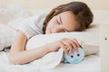 Cute teenage girl holding alarm clock under pillow