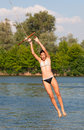Cute teenage girl jumping into the river Stock Image