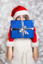 Cute teenage girl with santa hat holding blue gift box against snow background young caucasian and gloves looking at camera hiding Stock Photo