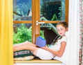 Cute teenage girl siiting on window siil and reading book Stock Photos