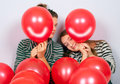 Cute teenage girls peeking behind smiling balloons Royalty Free Stock Photography