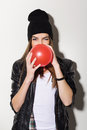 Cute teenage hipster girl with a red balloon attractive caucasian blowing wearing leather jacket and beanie hat Stock Photography