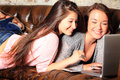 Cute teens networking two brunette teenage girls lounging on a couch laughing while looking at a computer Stock Photos