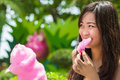 Cute thai girl is eating pink candyfloss with joy Stock Photography