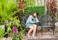 Cute thai girl is sitting lonely on the chair garden Stock Image