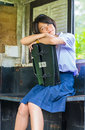 Cute thai schoolgirl is daydreaming in an old bus stop she hugging her school bag Royalty Free Stock Photos