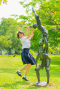 Cute thai schoolgirl is jumping with a statue in the park Stock Image