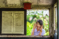 Cute thai schoolgirl is making a surprise through the panel old window will anyone get frighten Royalty Free Stock Images