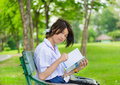 Cute thai schoolgirl is studying on a bench and smiling Royalty Free Stock Images