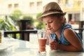 Cute thinking kid girl drinking tasty juice Royalty Free Stock Photo