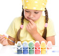 Cute thoughtful child play with paints while sitting at table isolated over white Royalty Free Stock Image