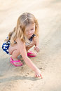 Cute thoughtful little girl with long blond hair squatting and drawing in the sand on the beach in summer day Stock Images