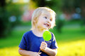 Cute toddler with big green lollipop Royalty Free Stock Photo