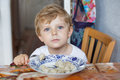Cute toddler boy of three years eating pasta at home kitchen Royalty Free Stock Photo