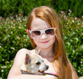 A cute toddler girl with colored sunglasses on holding her little dog Royalty Free Stock Photo