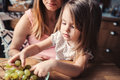 Cute toddler girl eating grapes with mother on the kitchen at home Royalty Free Stock Photos