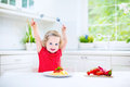 Cute toddler girl eating spaghetti in a white kitchen curly laughing red shirt playing with fork and spoon with tomato sauce and Stock Photos