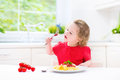 Cute toddler girl eating spaghetti in a white kitchen Royalty Free Stock Photo