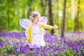 Cute toddler girl in fairy costume in bluebell forest adorable with curly hair wearing a with purple wings and yellow dress is Stock Image
