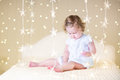 Cute toddler girl with her toy bear on a white bed between beautiful warm Christmas lights Royalty Free Stock Photo