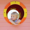Cute toddler girl hiding in playhouse at playground Royalty Free Stock Images