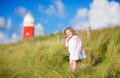 Cute toddler girl next to red lightshouse on beach Royalty Free Stock Photo