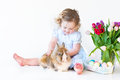 Cute toddler girl playig with a bunny on easter next to basket eggs Stock Photos