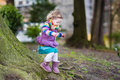 Cute toddler girl playing at big tree in spring park Royalty Free Stock Photo