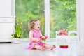 Cute toddler girl playing maracas in white room curly laughing a pink dress tambourine and a sunny with a big garden view window Stock Image