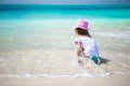 Cute toddler girl playing in shallow water at exotic beach standing Royalty Free Stock Photo