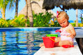 Cute toddler girl playing in swimming pool at Royalty Free Stock Photo