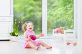 Cute toddler girl playing tambourine in white room curly laughing a pink dress and maracas a sunny with a big garden view window Royalty Free Stock Photos