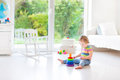 Cute toddler girl playing in a white room with big window into tt garden Stock Photos