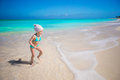 Cute toddler girl runing in shallow water at exotic beach standing Royalty Free Stock Photography