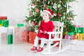 Cute toddler girl in santa hat sitting under christmas tree a red dress and a white rocking chair a white room with a big and many Royalty Free Stock Photo
