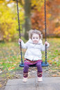 Cute toddler girl on swing with autumn trees Royalty Free Stock Photo