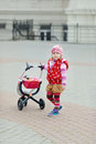 So cute toddler girl with toy stroller сute outside Royalty Free Stock Image