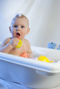 Cute toddler infant baby have fun playing bath white vertical family newborn skincare health Royalty Free Stock Photos