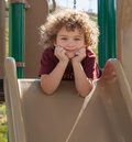 Cute toddler on slide a looks directly into your eyes just before coming down a Stock Images