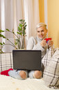 Cute trendy girl sitting on the couch with coffee and laptop Royalty Free Stock Photo