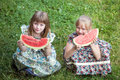 Cute two little girl eating watermelon on the grass in summertime Royalty Free Stock Photo