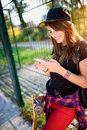 Cute urban girl in skate park with skateboard using smart phone Royalty Free Stock Photo