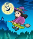 Cute witch on broom near castle Royalty Free Stock Image