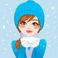 Cute woman blowing snowflakes in blue winter hat and warm clothing holding snow with hands close to her face softly Stock Image