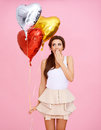 Cute woman with heart shaped party balloons Stock Images